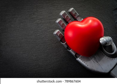 The desire to be human and loving the future concept with robot hand holding a heart against a dark background with copy space