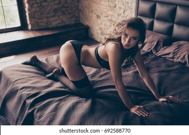Desire, passion, seduction, woman temptation concept. Young gorgeous brunette lady in bed in hot black outfit, so horny and naughty, cute and charming