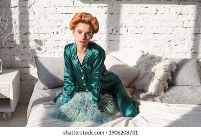 desire woman in pajamas and hair curlers sitting on bed in bedroom interior, sunlight