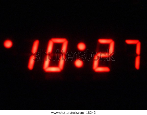 A desk alarm clock with bright red numbers in the dark.
