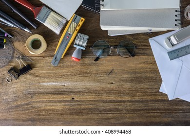 Desk of an artist with lots of stationery objects. Studio shot on wooden background,View from above.