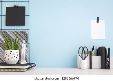 Desk with black and white objects and blue wall.