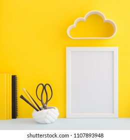 Desk with blank photo frame and school supplies over the yellow pastel background. Education, studing and back to school concept.