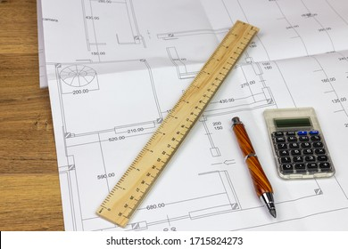 desk with building construction plan resting on top with ruler, pencil and calculator