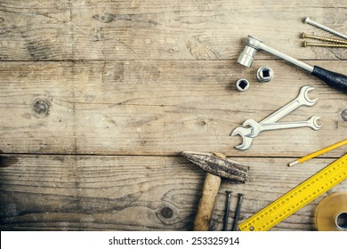 Desk of a carpenter with different tools. Studio shot on a wooden background.