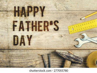 Desk of a carpenter with Happy fathers day sign. Studio shot on a wooden background.