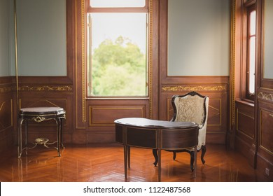 Desk and chair in antique office with warm lighting from windows