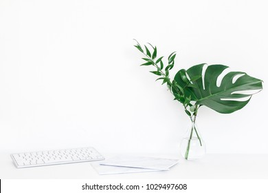 Desk with computer, notebook, green leaves. Creative workspace. Front view, copy space