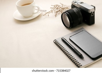 Desk with cup coffee,Phone,Notebook,Camera on white fabric,Top view with copy space.