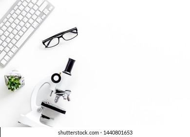 Desk of doctor in laboratory with microscope, keyboard for medical research on white background top view copyspace