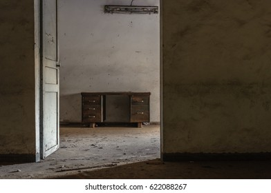 Desk in an empty room in an abandoned office building, looking through a doorway.