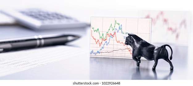 Desk with the figure of a bull and a graph with stock market price