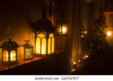 desk of free space and lamp with xmas tree in home . Christmas lantern in selective focus near window with holiday tree full of colored toys and lights. Night scene