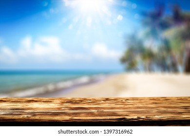 Desk of free space and summer background of beach with palms. Blue sku with sun light