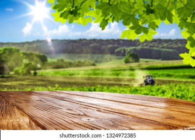Desk of free space for your natural product and spring landscape of farm with sunny day and blue sky.