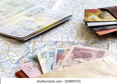 Desk of frequent traveler - angle view. The composition of essential items for trip: passport with entry stamps, cash notes of different countries, wallet with credit cards, and detailed map