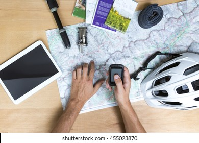 Desk with hands on a map, tablet pc and bike accessoires, elevated view