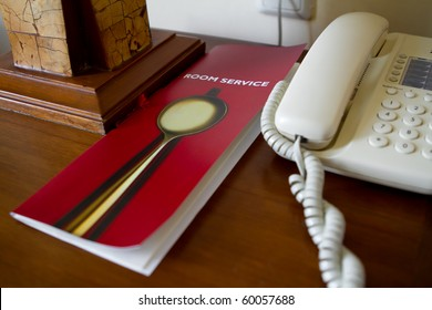 Desk of a hotel guest with room service list and telephone