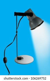 The Desk lamp on,isolated on blue background.
