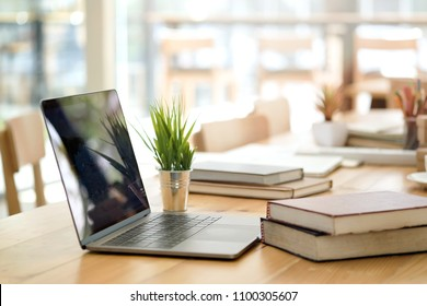 Desk with laptop, books and business office background.