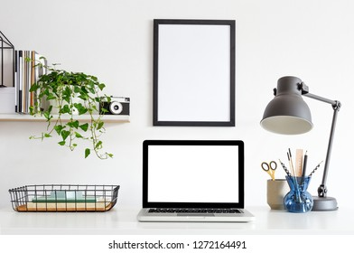 Desk with laptop computer, poster frame, supplies, notebooks, ivy on a shelf and white wall for mock up or copy space.