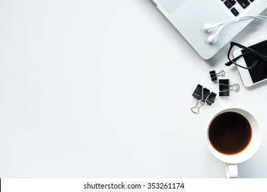 Desk with laptop, eye glasses, earphone, pen, document clips and a cup of coffee. Top view with copy space.