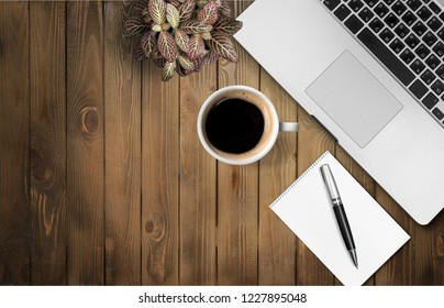 Desk with laptop, eyeglasses, notepad, pen and a cup of coffee on a old wooden table. Top view with copy space. Flat lay. Dark wooden background