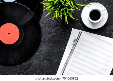 Desk of musician or dj with vynil records and blank paper for songwriter work on dark background top view mockup