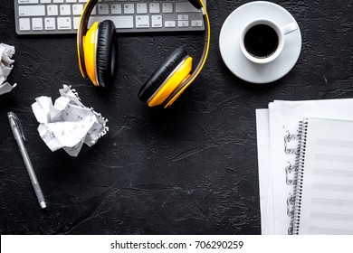 Desk of musician with headphones for songwriter work on dark background top view mockup
