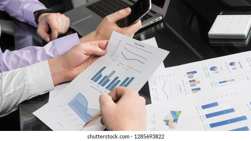 Desk in the office with charts, a laptop and men's hands