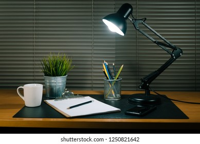 Desk office with clipboard, coffee cup and black table lamp,