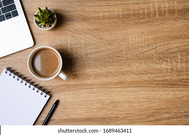 desk office with laptop, blank notepad, coffee cup and pen on wood table. Flat lay top view copy spce.
