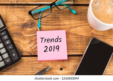 desk with paper, pen,  smartphone, glasses, coffee and calculator and german text Trends 2019