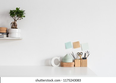Desk with school or office accessories on white wall background.
