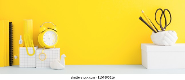Desk and school supplies over the yellow pastel background. Education, studing and back to school concept Creative desk with yellow wall and stationery.