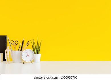 Schreibtisch und Schulbedarf auf gelbem Hintergrund. Erziehung, Lernen und zurück zur Schule Konzept Kreativität Schreibtisch mit gelber Wand und Schreibwaren.