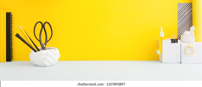Desk and school supplies with the yellow background. Education, studing and back to school concept Creative desk with yellow wall and stationery.