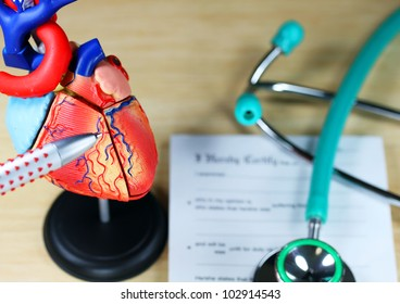 A doctor�s desk showing a green stethoscope, on a sick certificate pad in the background, and in the foreground the doctors pen point to a model of the heart, indicating where the patients problem is.