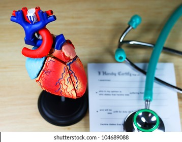A doctor�s desk showing a green stethoscope, resting on a sick certificate pad in the background, and in the foreground a detailed model of the human heart.