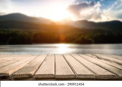 desk space and beautiful river with mountains and sun set background