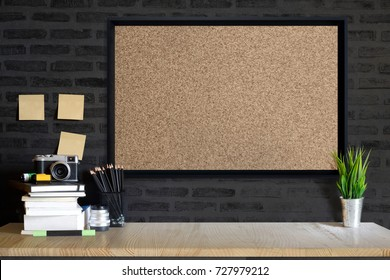 Desk space concept. Mock up Cork board, vintage camera and films on wood table workplace with supplies.