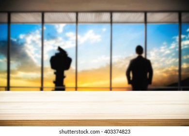 Desk space platform and business man standing in front of office window with tower and twilight sky sunset. For product display montage.