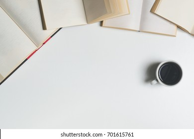 Desk or table full of open books and other supplies. Cup of coffee and glasses.View from above and a white background. Negative space.