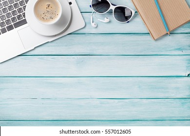 Desk table with laptop, coffee and sunglasses on wooden table. Workplace. Top view with copy space.