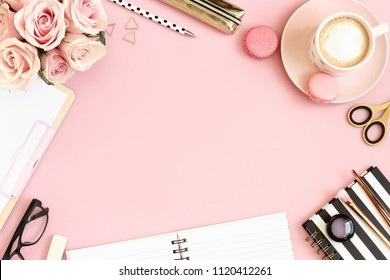 Desk table with pink roses, coffee cup, macaroons, spiral notebook, pen, pencils, scissors, glasses and makeup brushes.  Top view, flat lay with copy space.