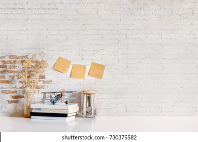 Desk with white brick wall, pencils in vintage airplanes toy and books. Mock up