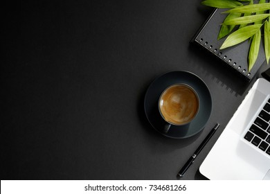 Desk workspace .desk dark workspace with black cup of coffee, laptop and plant on dark table.