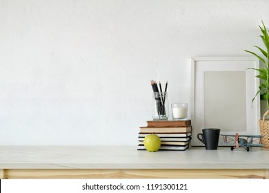 Desk workspace with mockup blank poster, supplies and copy space.