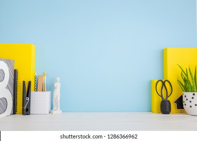Desk with yellow boxes, office objects and blue wall.