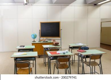 desks and blackboard in classroom at school